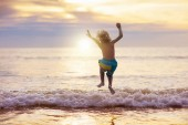 Fotografie Kind spielt am Strand. Kind bei Sonnenuntergang Meer.