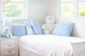 Fotografie Dětské postele v bílém sunny ložnici s oknem. Dětský pokoj a interiérového designu. Postel pro dítě nebo batole boy je doma. Ložní prádlo a textil pro děti školky. Architektury NAP a spánku čas
