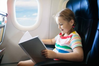 Child in airplane. Kid with book in air plane sitting in window seat. Flight entertainment for kids. Traveling with young children. Kids fly and travel. Family vacation. Girl reading book in airplane.