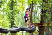 Kind im Wald-Erlebnispark. Kinder klettern auf einem Hochseilgarten. Agility und Klettern Outdoor-Vergnügungszentrum für Kinder. Kleines Mädchen beim Spielen im Freien. Schulhof-Spielplatz mit Seilbahn.