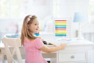 Child drawing rainbow. Kid painting at home. Little girl doing homework after school. Kids desk with abacus in white sunny bedroom. Children study, learn to read and write. Bedroom for young student.