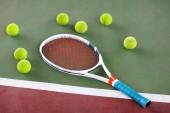 Tenisovou raketu a míček na venkovním hřišti po zápase. Spousta kuličky na zemi po tenisový trénink v sportovního klubu. Sportovní zařízení po zápase. Zdravé letní aktivity.