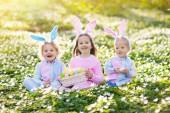 Velikonoční vajíčka v jarní zahradě. Děti hledání barevná vajíčka a sladkosti v kvetoucí květinové pole skryté. Děti s uši zajíček a košík na vajíčka. Rodinné oslavy Velikonoc. Chlapec a dívka hra.