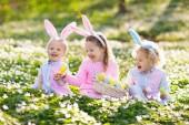 Kinder mit Hasenohren auf Ostereiersuche.