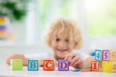Child learning letters. Kid with wooden abc blocks