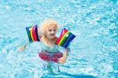 Kind im Schwimmbad. Kind mit Schwimmarmbinden.