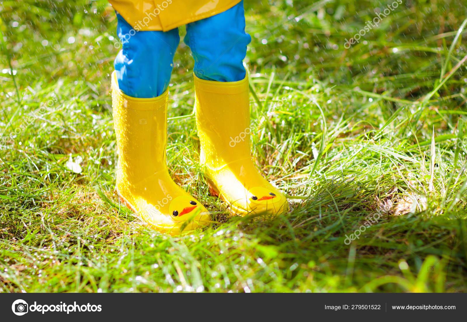 Bambino che gioca sotto la pioggia. Ragazzo con ombrello
