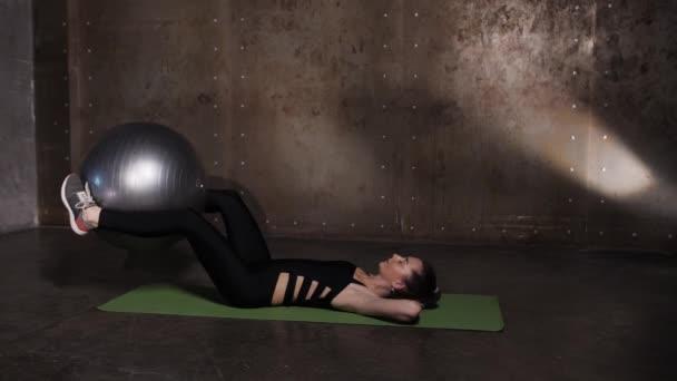 athletisch schöne Frau macht Übungen in der Turnhalle, Studio-Trainingsprogramm.