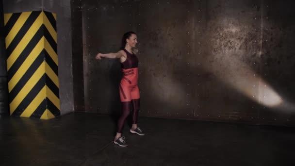 Atletická krásná žena provádí cvičení v tělocvičně, cvičný výcvik.