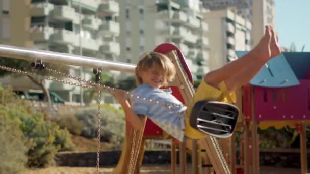 Šťastné děti se houpá venku. Chlapec a dívka se baví na hřišti.