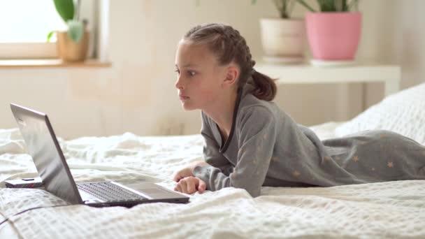 Roztomilé dítě používat notebook pro vzdělávání, on-line studium, domácí studium. Holka má domácí úkoly ve škole.