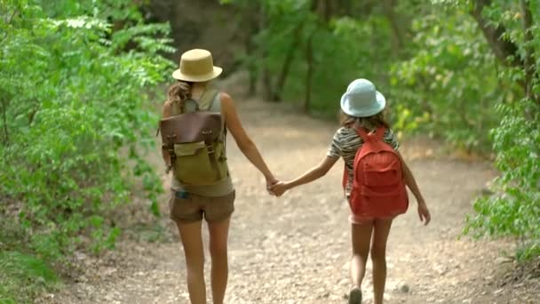 Žena s batohem kráčí s dívkou na silnici v horách. Cestování životní styl koncept dobrodružství venkovní letní prázdniny. Šťastná rodinná turistika na venkově.