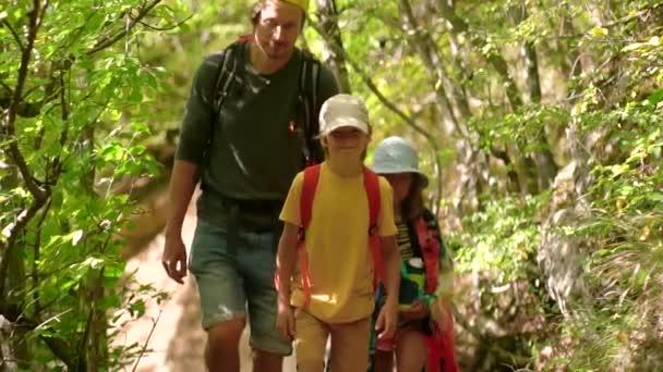 Egy férfi hátizsákkal, aki fiúkkal és lányokkal sétál a hegyekben. Utazási életmód koncepció kaland szabadtéri nyári vakáció. Boldog családi kirándulás vidéken