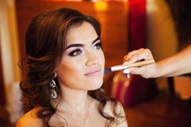 Makeup artist preparing bride before her wedding