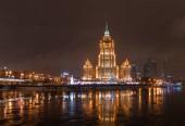 Modern épületek a megvilágítás este folyó a háttérben