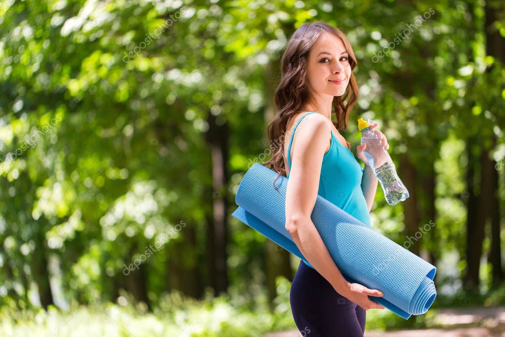 Beautiful smiling woman with a yoga mat outdoors. Concept of healthy lifestyle, yoga and sports.