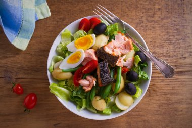 Salad Nicoise with salmon. Tomato, green beans, new potato, olives and lettuce salad with salmon. overhead, horizontal