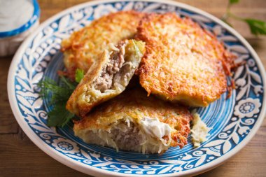 Potato Pancakes Filled With Meat. Vegetable fritters stuffed with meat on blue plate and sour cream or yogurt