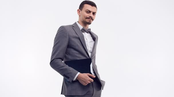 Portrait of handsome young confident arabic businessman with fancy mustache in fashion gray suit holding tablet isolated on white studio background