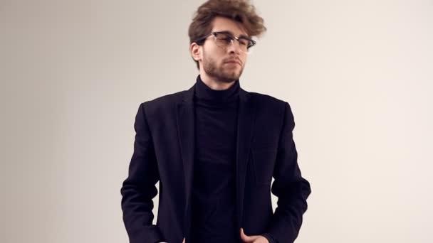 Göndör haja visel öltönyt és szemüveg szürke háttér stúdióban szép elegáns férfi divat portréja