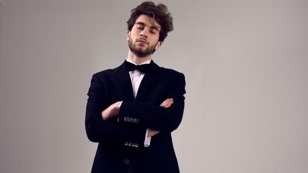 Módní portrét pohledný elegantní muž s kudrnatými vlasy nosit smoking pózuje na šedém pozadí ve studiu