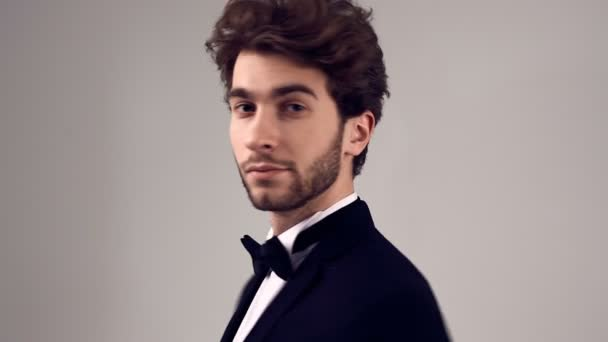 Fashion portrait of handsome elegant man with curly hair wearing tuxedo posing on gray background in studio