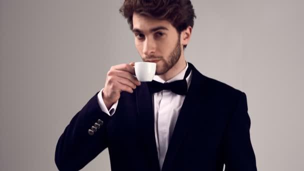 Göndör haj, viselt szmoking gazdaság egy csésze eszpresszó szürke háttér stúdióban szép elegáns férfi divat-portré