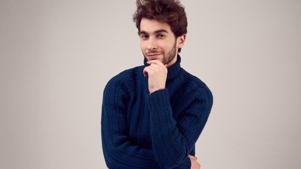 Divat-portré, szép elegáns férfi göndör haj kék pulóver elszigetelt fehér background