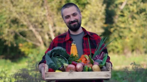 Farmer kezében fadoboz tele zöldséggel a biogazdaságban. Mosolygó fehér szakállas férfi portréja a kertben.