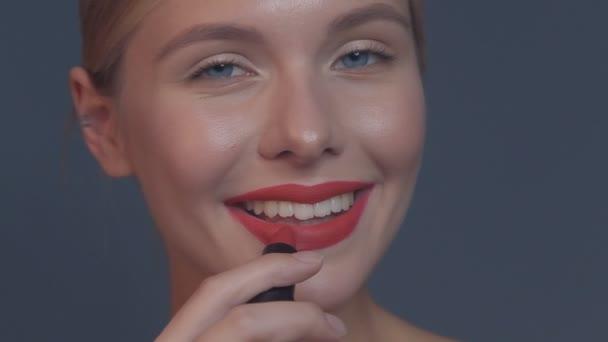 schöne Mädchen mit roten Lippen und klassischem Make-up mit Lippenstift in der Hand posiert im Studio. Schönheit Gesicht.