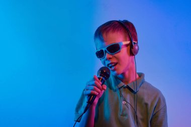 Caucasian teen boy portrait on blue neon light. Male model with microphone. Concept of human emotions, music.
