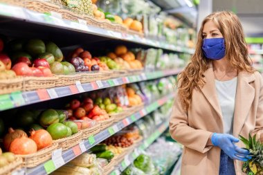 Shopping during the coronavirus Covid-19 pandemic. Woman in facial mask and gloves buys citrus fruit at market. stock vector