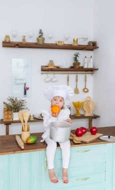 Little beautiful girl in a cook cap sits on a kitchen table and eats big orange fruit. Concept of healthy food and healthy lifestyle.