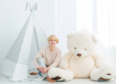 Mature woman sitting on a floor with a toy teddy