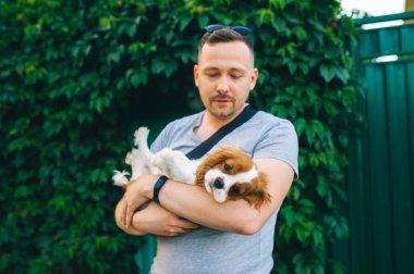 Caucasian man standing on a yard and hugging his his King Charles spaniel puppy