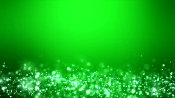 Video animation of christmas light shine particles bokeh over green background - holiday concept