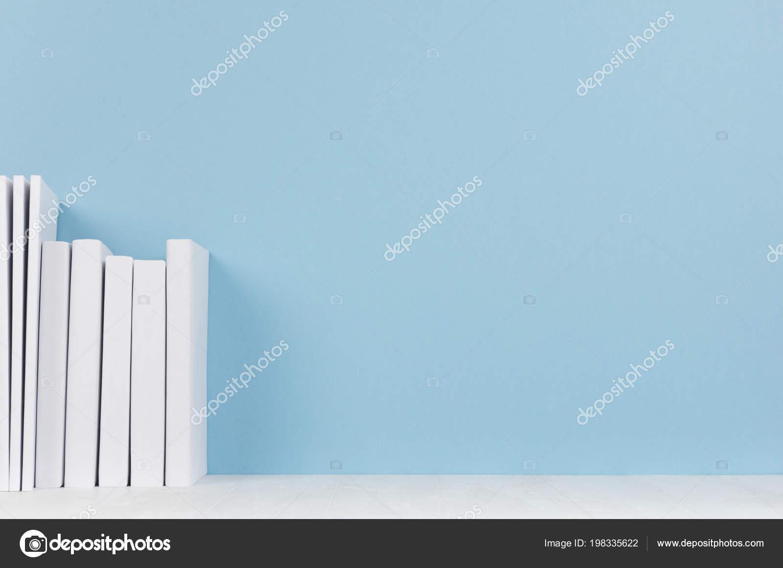 Rangée livres blancs sur bureau bois clair fond bleu doux
