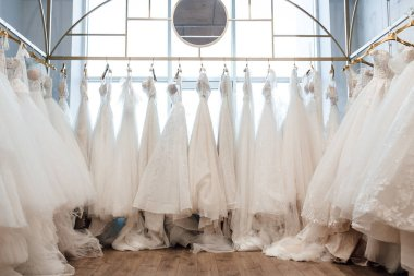 beautiful white wedding dresses on hangers in the store