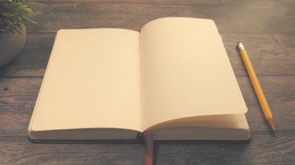 Horní pohled na otevřený deník a žlutou tužku na stole