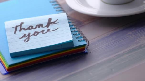 Blaue Haftnotiz mit Dankeschön auf Holztisch