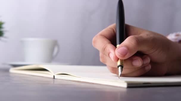Közelkép a nők kezét tollal írás a naplóba