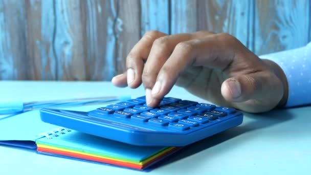 Close up of man hand using calculator on office desk