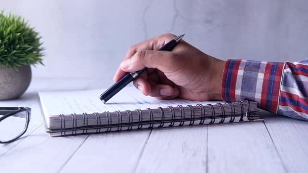 man kézírás tollal a papíron