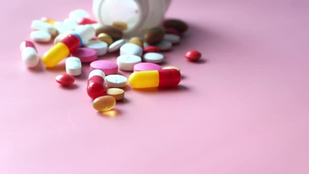 colorful pills spilling on pink background
