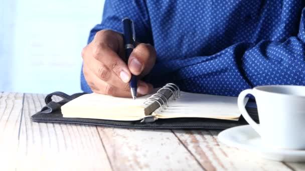 Üzletember kézírás tollal jegyzettömbön