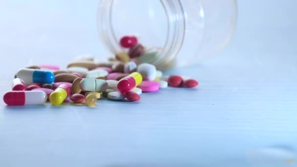 colorful pills spilling from a container on table