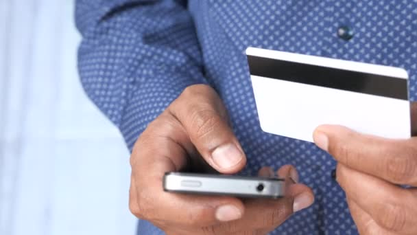 Muž ruka drží kreditní kartu a pomocí chytrého telefonu nakupování on-line