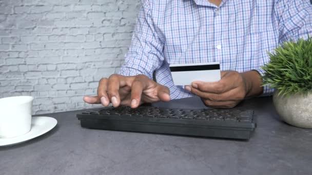 Mann hält Kreditkarte in der Hand und benutzt Tastatur beim Online-Shopping