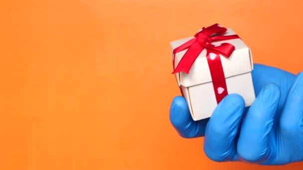 mužská ruka v modré lékařské rukavici dává dárek.