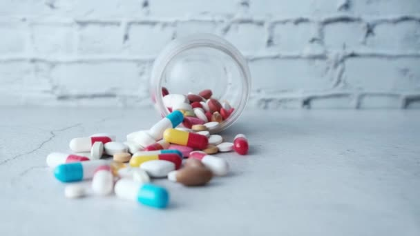 close up of colorful pills spilling on white background